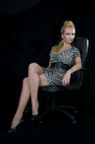 Cold beauty on black arm-chair. Young blond woman in dress on arm-chair, professional hair and makeup, on dark background stock photography