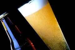 Cold Beer. Beer bottle and glass with freshly poured beer Royalty Free Stock Photography