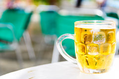 Cold beer. Glass of cold beer on table of street cafe Royalty Free Stock Images