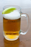 Cold beer. Cold glass of beer with a lime Royalty Free Stock Photography