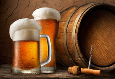 Cold beer and barrel. Cold beer and wooden barrel in cellar royalty free stock images