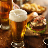 Cold beer with foamy head and burgers Stock Photo