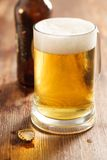 Cold beer glass on bar or pub desk. Bottle of beer on background Royalty Free Stock Photos