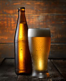 Cold beer in glass and bottle on a dark wooden background Stock Images