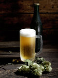 Cold  beer in glass, bottle and hops on a dark wooden background Royalty Free Stock Photography
