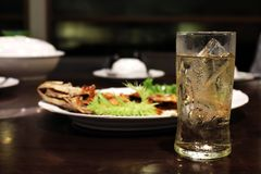 Cold Beer in glass and ice and food on table, Beer is Beverage Alcohol in foods shop night time selective focus royalty free stock photography