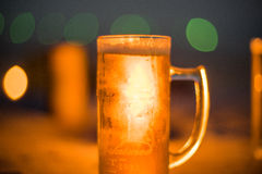 A cold beer in a hot summer night. A cool glass of beer in a hot Asian summer night with beautiful bokeh lights in the background stock photo