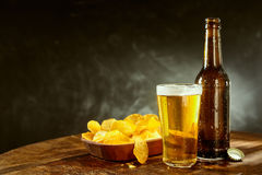 Cold beer and potato crisps on a bar counter Royalty Free Stock Photo