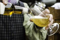 Cold beer pouring into glass. Hand holds beer bottle and fills the glass Stock Images