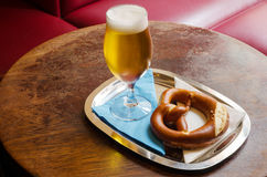 A cold beer with pretzel in a restaurant. A glass of cold beer and a pretzel served on a metal tray with white and blue serviettes on an old wooden table in a Stock Photography