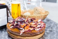 Cold beer and Wooden plate of galician style cooked octopus with paprika and olive oil. Pulpo a la gallega. Cold beer and Wooden plate of galician style cooked stock images