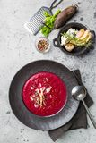 Cold Beetroot creamy soup. Cold Beetroot mashed soup with cream, apple, cheese and thyme in a dark bowl over stone background, top view royalty free stock photos