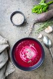 Cold Beetroot creamy soup. Cold Beetroot mashed soup with cream, apple, cheese and thyme in a dark bowl over stone background, top view royalty free stock photo
