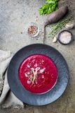 Cold Beetroot creamy soup. Cold Beetroot mashed soup with cream, apple, cheese and thyme in a dark bowl over stone background, top view stock photography