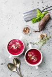 Cold Beetroot creamy soup. Cold Beetroot mashed soup with cream, apple, cheese and thyme in a white bowl over stone background, top view stock photo
