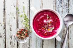 Cold Beetroot creamy soup. Cold Beetroot mashed soup with cream, apple, cheese and thyme in a white bowl over wooden background, top view royalty free stock image