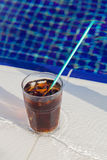 Cold beverage on the edge of swimming pool Royalty Free Stock Photo