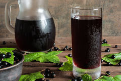 Cold black currant juice in a glass and pitcher on wooden table Stock Images