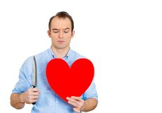 Cold blooded guy holding knife and heart Royalty Free Stock Photography