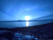 Cold blue fjord and snowy mountain landscape with sunset Stock Images