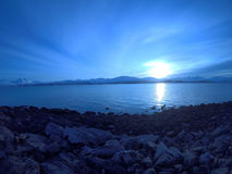 Cold blue fjord and snowy mountain landscape with sunset Royalty Free Stock Photography