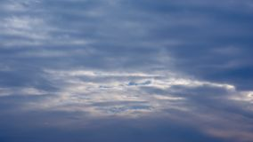 Cold blue grey storm clouds background. Dark blue grey storm clouds with lighter sun spots weather background royalty free stock image