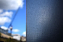 Cold blue steel against blue sky with construction crane Royalty Free Stock Photography