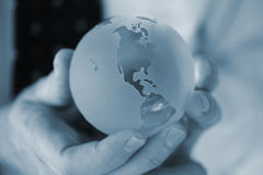Cold Blue World. Glass globe showing the Americas, being held in both hands in a blue hue stock photography