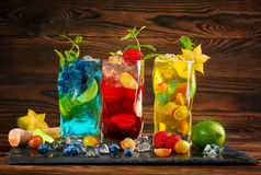 Cold blue and yellow mojitos. Red mojito with mint. Mojito with rum. Alcohol on a wooden background. Summer drinks and cocktails. stock photography