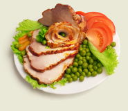 Cold boiled pork decorated.. Cold boiled pork decorated with salad, tomatoes and green pea on the plate over white background Stock Photos