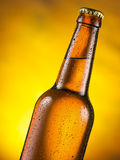 Cold bottle of beer with condensed moisture on it. Yellow background Royalty Free Stock Image