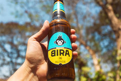 Cold bottle of India`s craft beer Bira 91 in a hand of drinker. Young company B9 Beverages owns Bira 91. GOA, INDIA - FEB 28: Cold bottle of Indian craft blonde Royalty Free Stock Photography