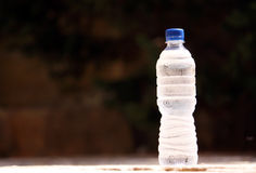 Cold bottle of water. A cold bottle of water with condensation on the bottle against a natural background Stock Photography