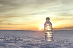 Cold bottle of water. In the snow at sunset Stock Photos