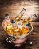 Cold bottles of beer in the brazen bucket. Cold bottles of beer in the brazen bucket on the wooden table Stock Photos