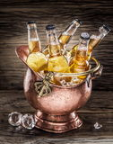Cold bottles of beer in the brazen bucket. Cold bottles of beer in the brazen bucket on the wooden table Royalty Free Stock Image