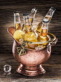 Cold bottles of beer in the brazen bucket. Cold bottles of beer in the brazen bucket on the wooden table Stock Photo