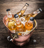 Cold bottles of beer in the brazen bucket. Cold bottles of beer in the brazen bucket on the wooden table Royalty Free Stock Photos