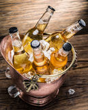 Cold bottles of beer in the brazen bucket. Cold bottles of beer in the brazen bucket on the wooden table Stock Images