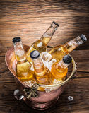 Cold bottles of beer in the brazen bucket. Cold bottles of beer in the brazen bucket on the wooden table Royalty Free Stock Photo