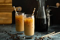 Cold brew iced coffee in tall glasses. Refreshing cold brew iced coffee in tall glasses with milk or creamer on dark background stock photography