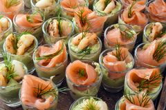 Cold buffet with appetizers in glasses, prawn shrimps and salmon. On avocado cream, view from above, selected focus, narrow depth of field Royalty Free Stock Images