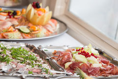 Cold buffet detail. Detail of cold buffet food, with meats and various fruits on silver plates Stock Photo