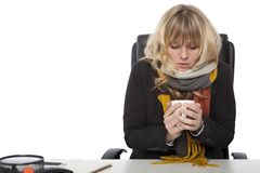 Cold businesswoman drinking hot coffee Royalty Free Stock Image