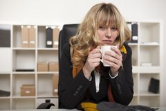 Cold businesswoman warming up with coffee Royalty Free Stock Photo