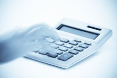 Cold Calculations. Calculator with blank screen and hand with motion blur operating buttons, cold tone Royalty Free Stock Photos