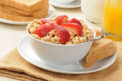 Cold cereal topped with strawberries Stock Images