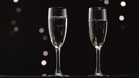Cold champagne poured into two transparent glass of the bottle. Bokeh blinking black background. Cold champagne poured into two transparent glass bottles in stock video