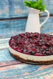 Cold cheesecake with cherry jelly on table Stock Image