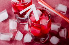 Cold cherry drink with ice cubes and cocktail tubes in glasses, on pink background Stock Images